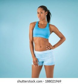 African American woman with blue workout clothing and blue background, studio shot.