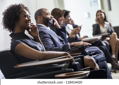 African American woman or businesswoman using cell phone in busy airport with other people in background