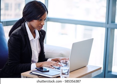 African American woman busy sitting and typing on her notebook while seated on a sofa in a business lounge in the airport.