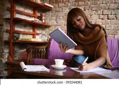 African American woman calculating her bills.