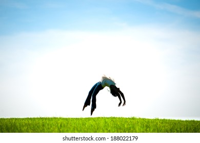 African American woman captured in mid-air doing a back flip in a fresh Spring field. Silhouetted.