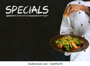 African American woman chef with chalk specials sign on blackboard background