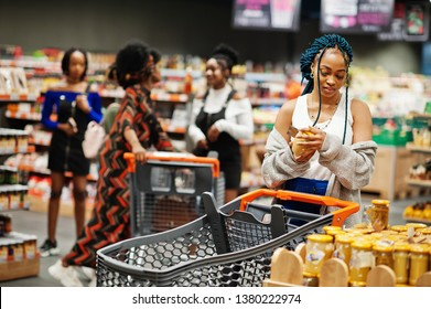 African american woman choose honey pot at supermarket against her afro friends with shopping cart.