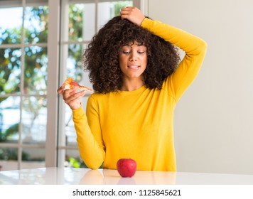 African american woman choosing between apple and pizza slice stressed with hand on head, shocked with shame and surprise face, angry and frustrated. Fear and upset for mistake.