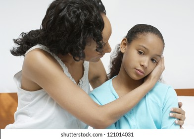 African American woman comforting sick daughter at home