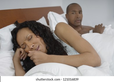 African American woman coughing in bed with man in background