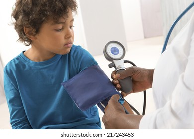African American woman doctor taking a child blood pressure.