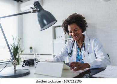Afroamerikanischer Frauenarzt, der in ihrem Büro online mit tragbaren Informationen arbeitet. Telemedizin. Beratung in der Grundversorgung, Psychotherapie, Notfalldienste.