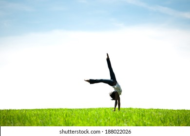 African American woman doing hand stand in field of fresh grass.