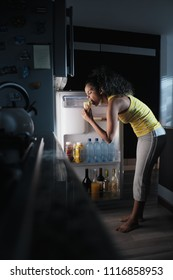 African american woman doing midnight snack at home. She eats a sandwich and looks for food into the refrigerator at night.
