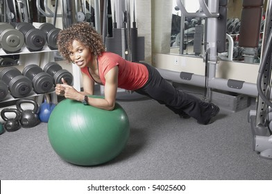 African American woman doing plank exercise on a gym ball