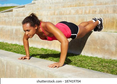 African American Woman Doing Push Ups In Park On Steps. Copy space, color image, mixed race woman working out horizontal shot.