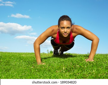 African American Woman Doing Push Ups In Park. Copy space, color image, mixed race woman working out horizontal shot.