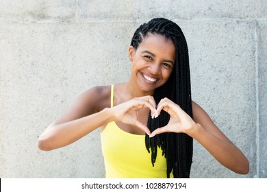 African American woman with dreadlocks in love showing heart with hands outdoors in the summer