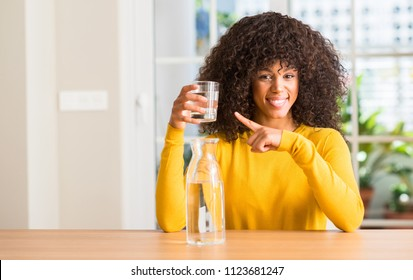 African american woman drinking a glass of water at home very happy pointing with hand and finger