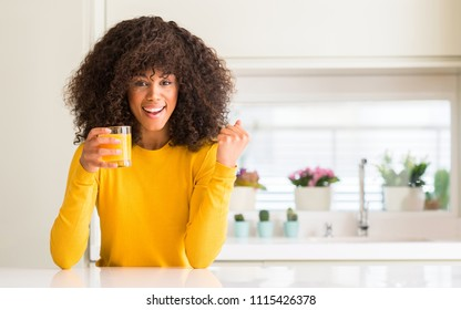 African american woman drinking orange juice in a glass screaming proud and celebrating victory and success very excited, cheering emotion