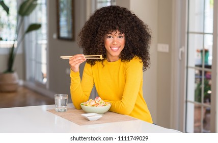 African american woman eating asian rice at home with a happy face standing and smiling with a confident smile showing teeth