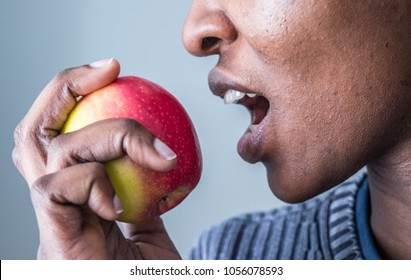 African American  woman eating biting a pink lady apple, isolated against white background healthy eating weight loss concept.  Adam and Eve. Forbidden fruit concept