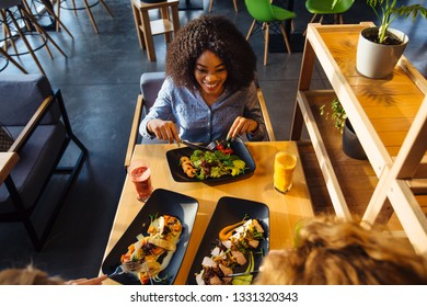 African american woman eating in cafe or restaurant with friends