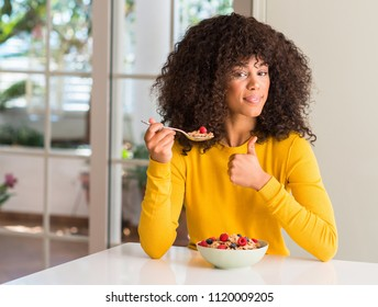 African american woman eating cereals, raspberries and blueberries happy with big smile doing ok sign, thumb up with fingers, excellent sign