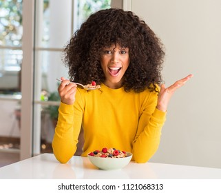 African american woman eating cereals, raspberries and blueberries very happy and excited, winner expression celebrating victory screaming with big smile and raised hands