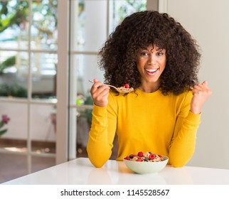African american woman eating cereals, raspberries and blueberries screaming proud and celebrating victory and success very excited, cheering emotion