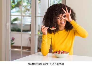 African american woman eating cereals, raspberries and blueberries with happy face smiling doing ok sign with hand on eye looking through fingers