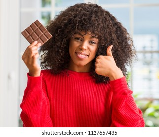 African american woman eating chocolate bar at home happy with big smile doing ok sign, thumb up with fingers, excellent sign