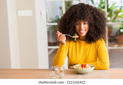 African american woman eating pasta salad at home with a happy face standing and smiling with a confident smile showing teeth