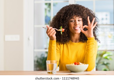 African american woman eating pasta salad at home doing ok sign with fingers, excellent symbol