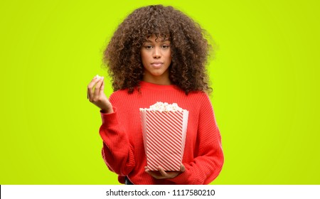 African american woman eating popcorn with a confident expression on smart face thinking serious