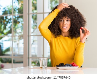 African american woman eating raspberries and blueberries at home stressed with hand on head, shocked with shame and surprise face, angry and frustrated. Fear and upset for mistake.