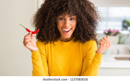African american woman eating red hot chili pepper screaming proud and celebrating victory and success very excited, cheering emotion