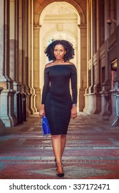 African American Woman Fashion in New York. Wearing long sleeve, slim, off shoulder dress, carrying blue bag, young lady walking on vintage style, narrow street, going to work. Instagram effect.