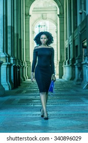 African American Woman Fashion in New York. Wearing long sleeve, slim, off shoulder dress, carrying blue bag, a young lady walking on narrow street, going to work. Filtered look with cyan tint.