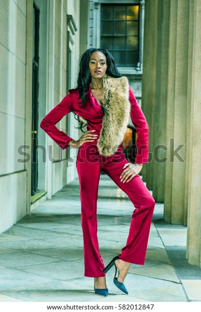 African American Woman Fashion in New York. Lady dressing in red slim fashionable jacket, pants, black high heel pumps shoes, faux fur scarf on shoulder, stands outside office. Color filtered effect