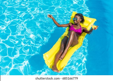African american woman floating with cocktail on inflatable mattress in swimming pool