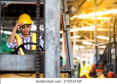 African american Woman forklift worker operator driving vehicle wearing safety goggles and hard hat at warehouse