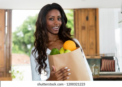 African american woman with fresh and healthy fruits at home at kitchen