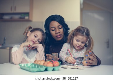 African American woman helps girls to decorations Easter Egg.
