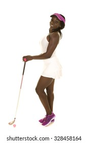an African American woman in her golf clothing, with her club and ball.