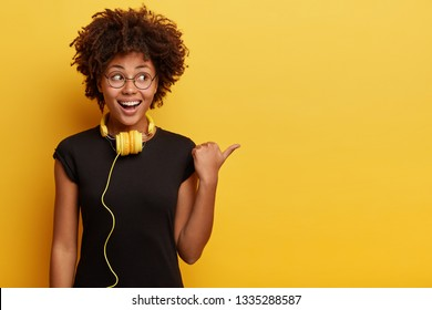 African American woman in high spirit points away with thumb, feels entertained and satisfied, listens radio broadcasting with modern headphones connected to telephone, checks sound, shows free space