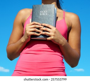 African American Woman Holding Bible Which Is The Word Of God, Sharper Than Any Double Edged Sword, Piercing Through Bone And Marrow, Which is The Sword Of The Spirit.