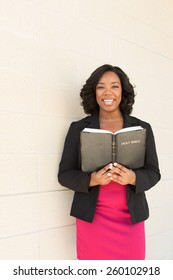 African American woman holding a Bible looking at the camera and smiling.