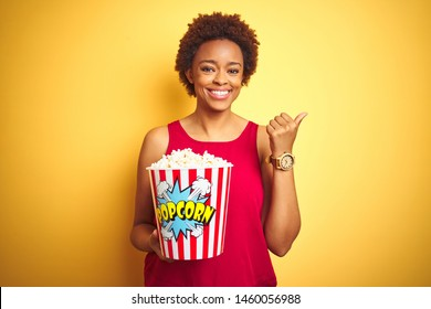 African american woman holding pack of popcorn over yellow isolated background pointing and showing with thumb up to the side with happy face smiling