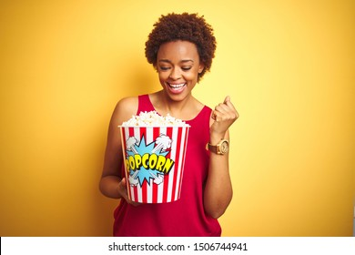 African american woman holding pack of popcorn over yellow isolated background screaming proud and celebrating victory and success very excited, cheering emotion