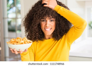 African american woman holding a plate with potato chips at home stressed with hand on head, shocked with shame and surprise face, angry and frustrated. Fear and upset for mistake.