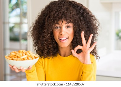 African american woman holding a plate with potato chips at home doing ok sign with fingers, excellent symbol