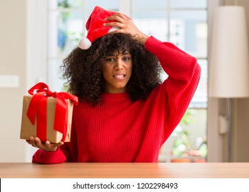 African american woman holding present wearing christmas red hat stressed with hand on head, shocked with shame and surprise face, angry and frustrated. Fear and upset for mistake.