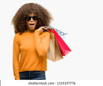 African american woman holding shopping bags scared in shock with a surprise face, afraid and excited with fear expression
